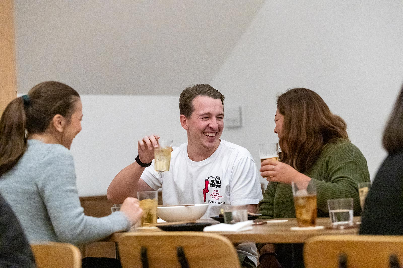 Group of three people at dinner talking and laughing together