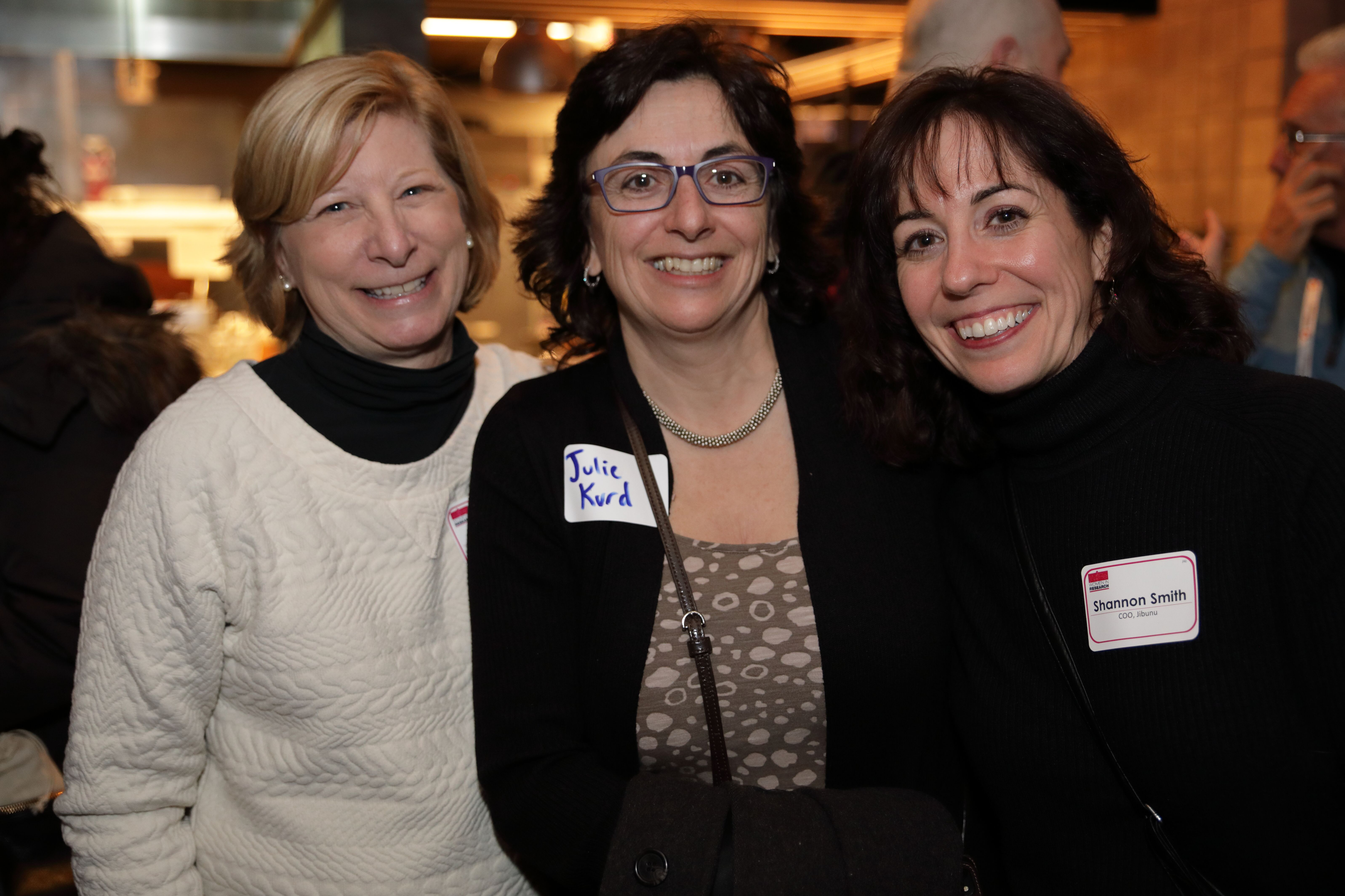 Three women smiling at a Women in Research event