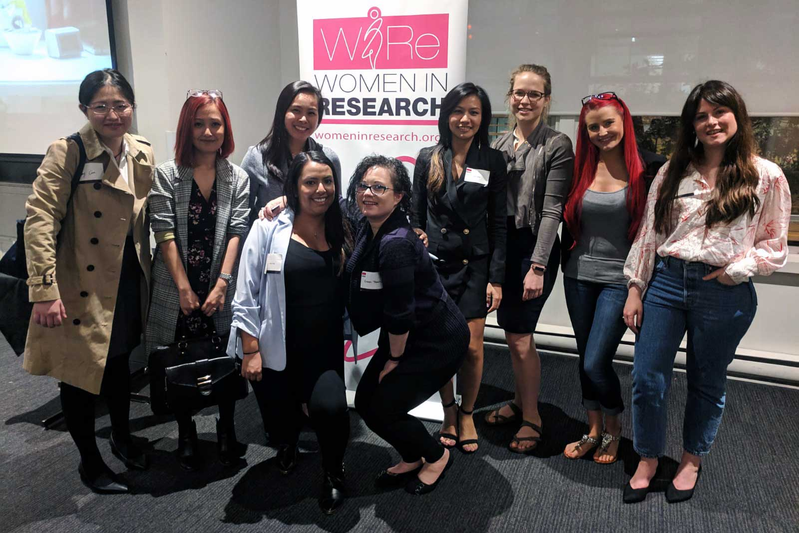 A group of women posing in front of a Women in Research Banner