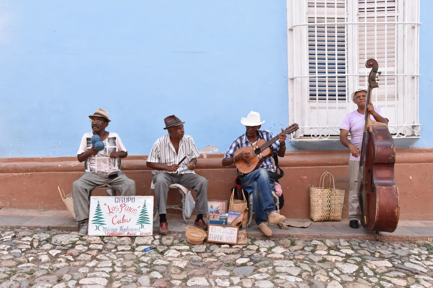 4 men are playing music in the streets of Trinidad