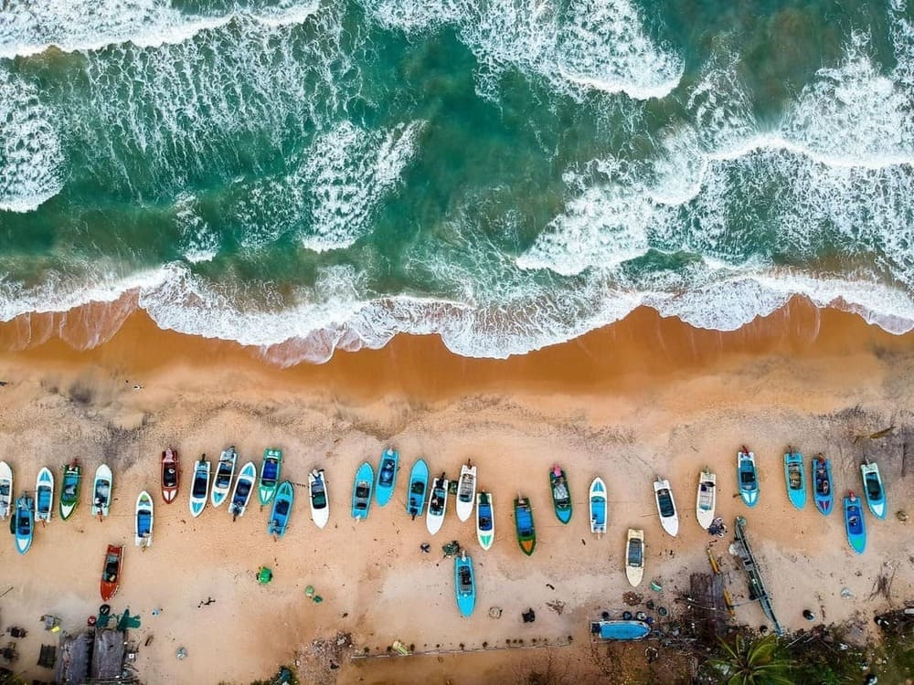 A drone shot from a beach with boats in Sri Lanka