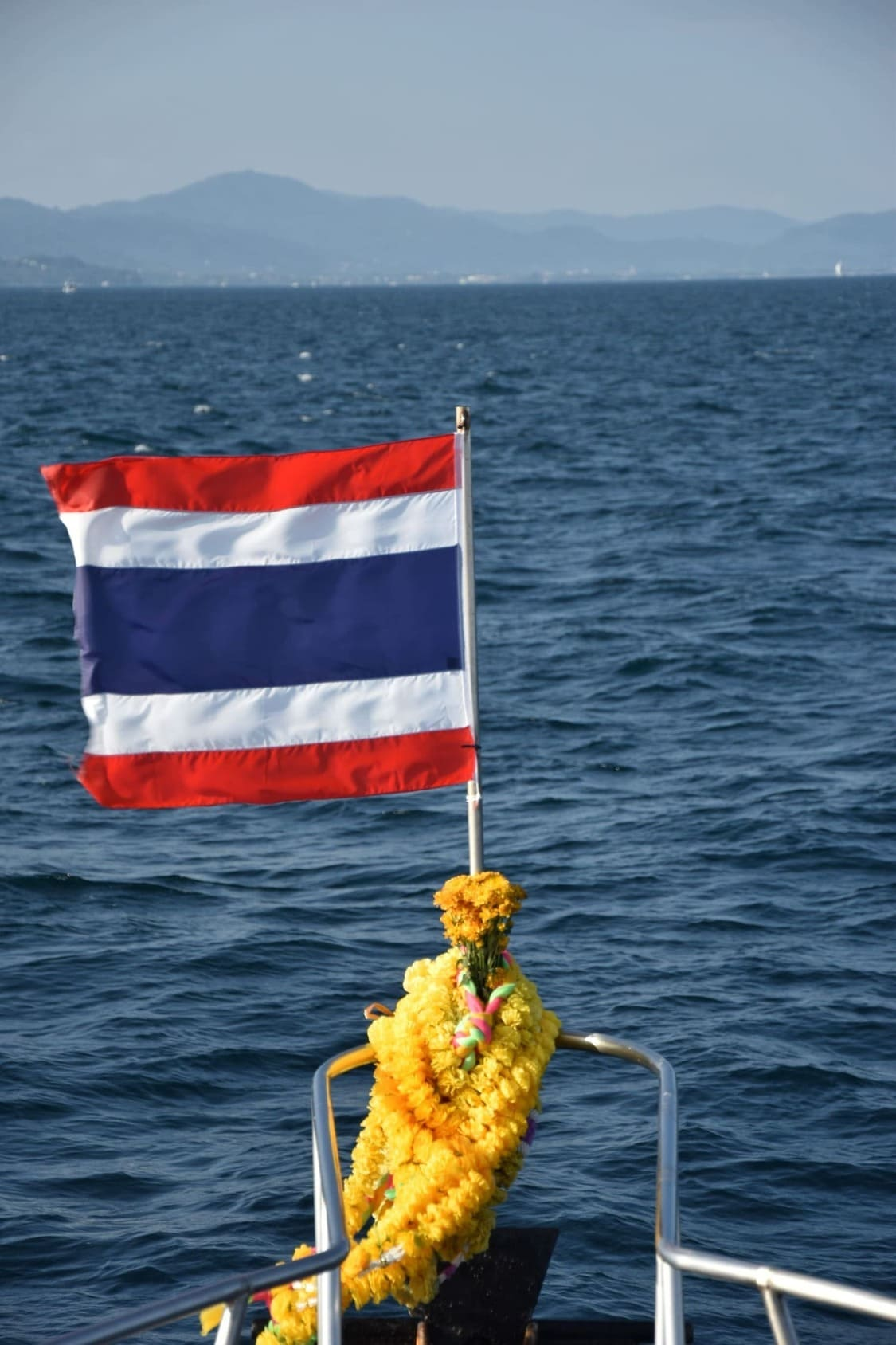 The flag of Thailand on front of a liveaboard