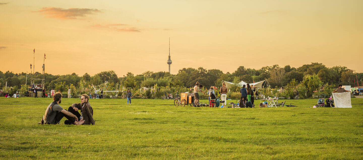 Photo with people at the Tempelhofer Feld during sunset and the Television Tower in the background.