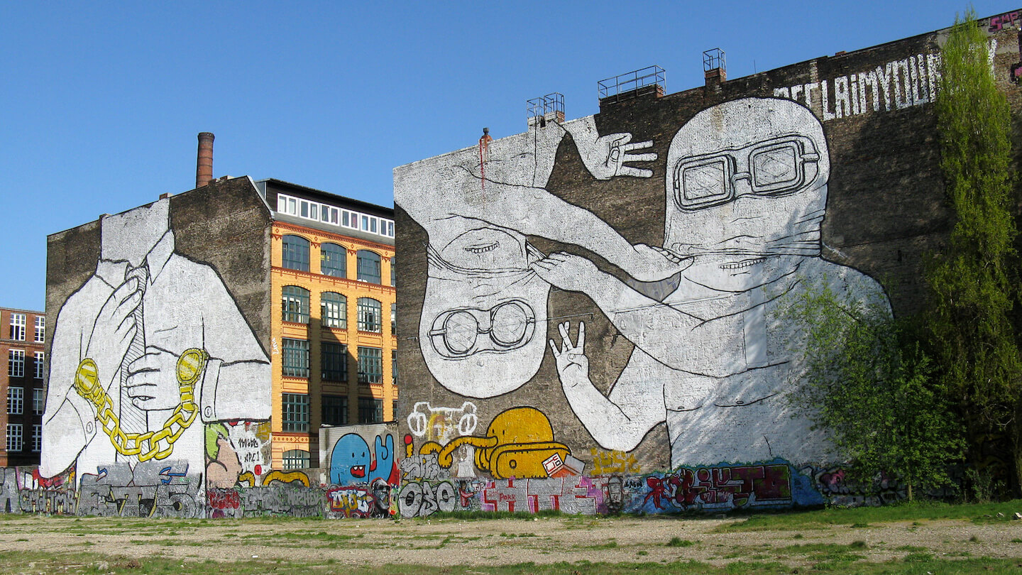 Photo of two huge wall paintings and various graffitis in front of an empty space