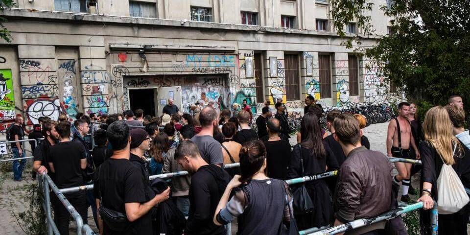 Photo of a long queue in front of the Berghain club all dressed in black.