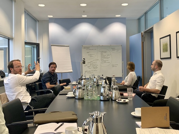 My team during a visit at the German ministry for justice. People are sitting at a big desk while Conrad is explaining something. A whiteboard in the background.