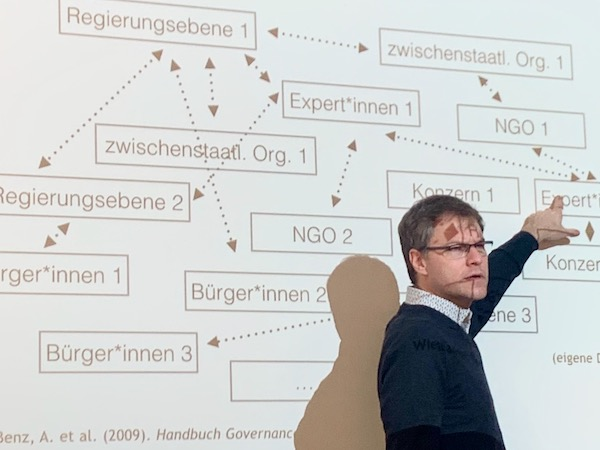 Photo of one my professor Tobias Schröder during of his presentations with slides in the background.