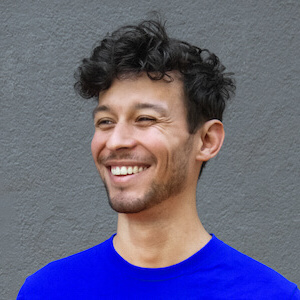 Portrait photo of José Ernesto Rodríguez smiling with short and slightly curly hair in a blue t-shirt.