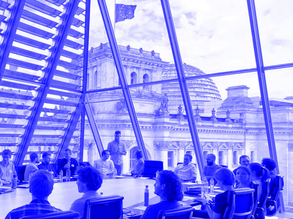 About a dozen of people sitting at a big table in a house with a glazed facade and the Reichstag in the background.