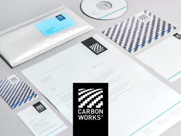 Photo of various branded elements such as a letterhead, envelope, business card, postcard and CD