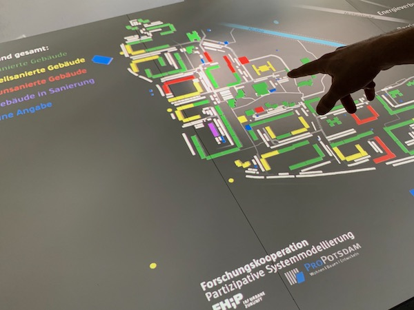 Photo of an interactive table showing architectural data and a hand pointing to one of the houses
