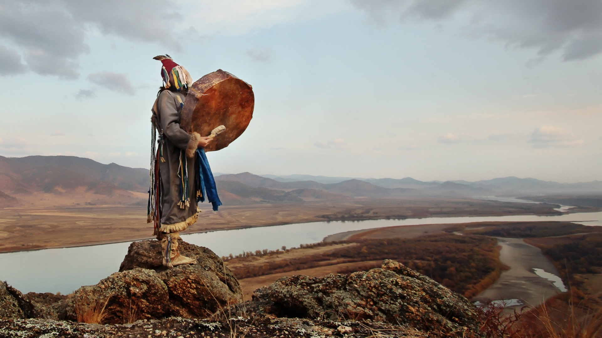 shaman with a drum and feathers in the mountain
