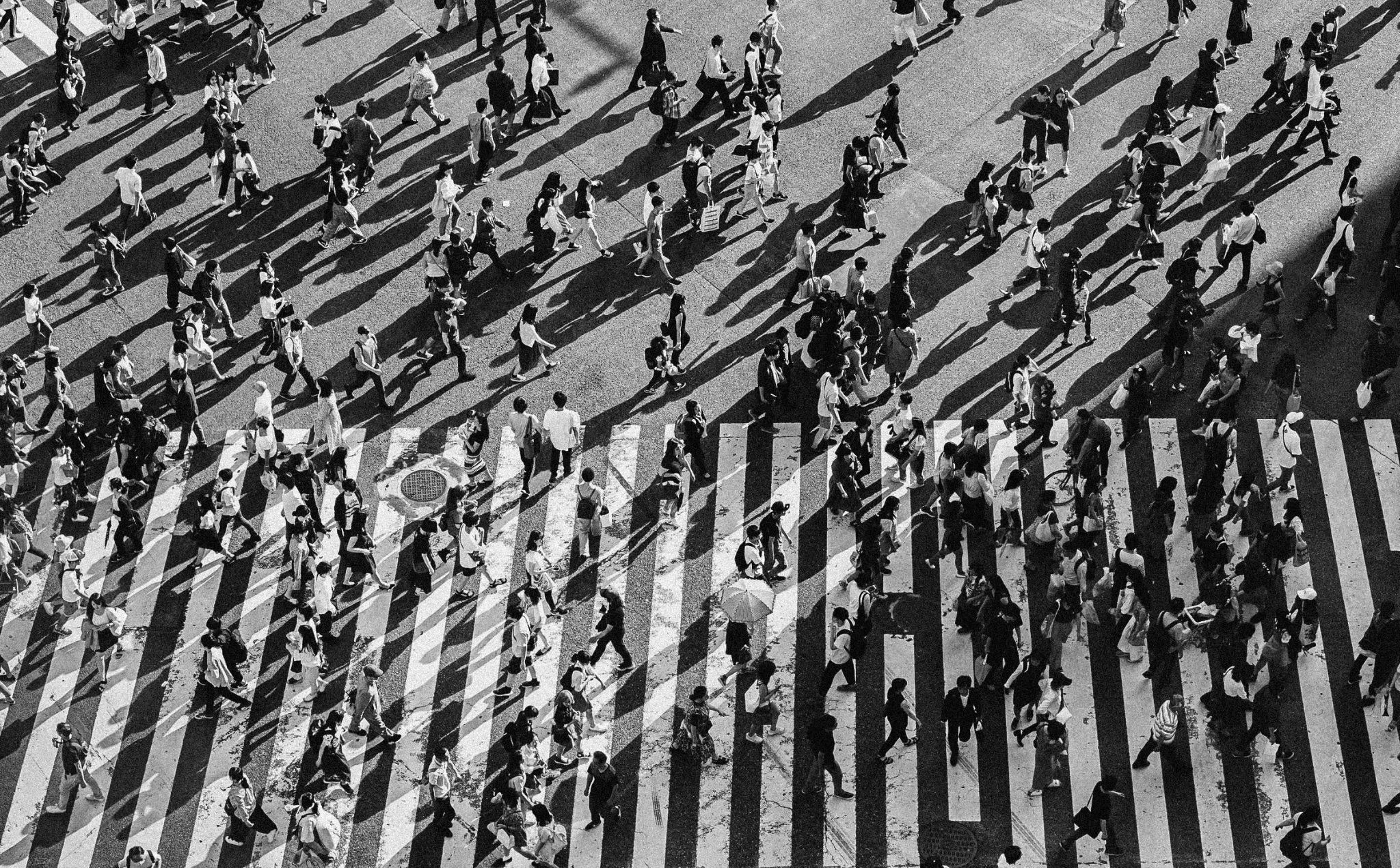 black and white photo of a street in tokyo Jaywalking laws are a stark reminder that many urban spaces are designed primarily for motorized (and non-human) vehicles. Pictured here is the Shibuya Crossing in Tokyo.