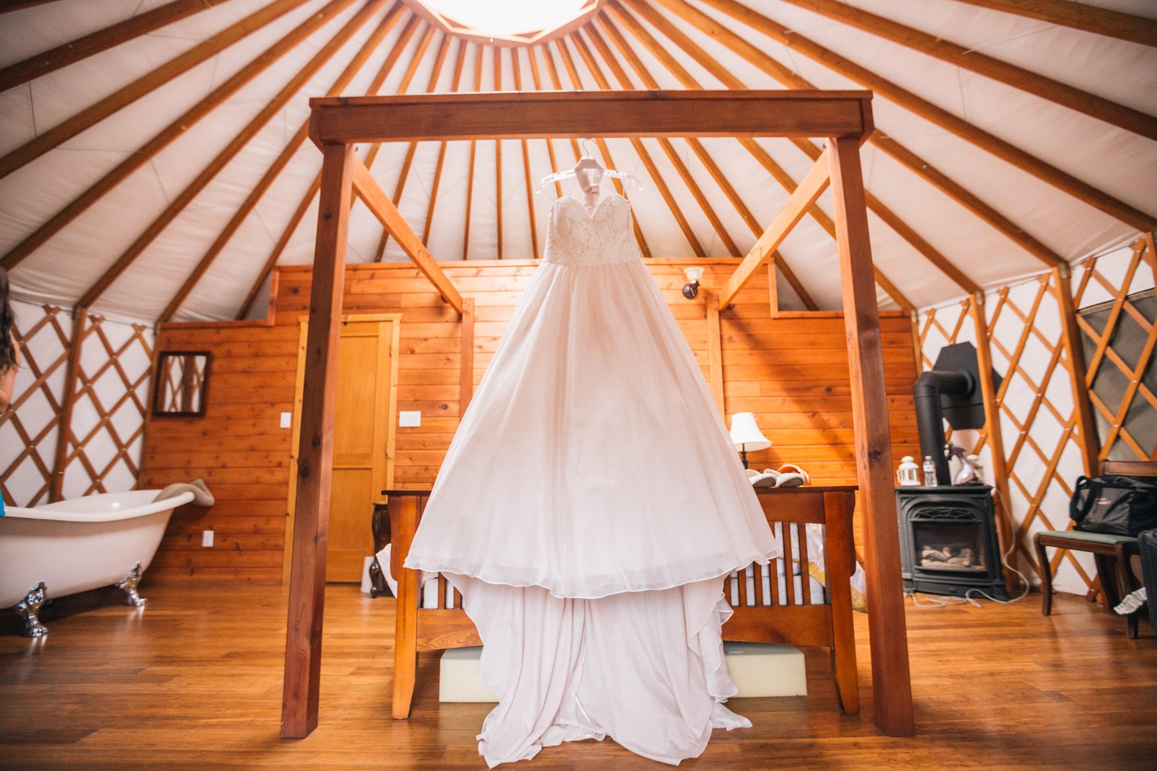Interior of yarlington bridal suite yurt, wedding dress hanging above bed - Merridale Wedding Venue Vancouver Island- taken by Marlboro Wang Photo | Focal bookfocal.com