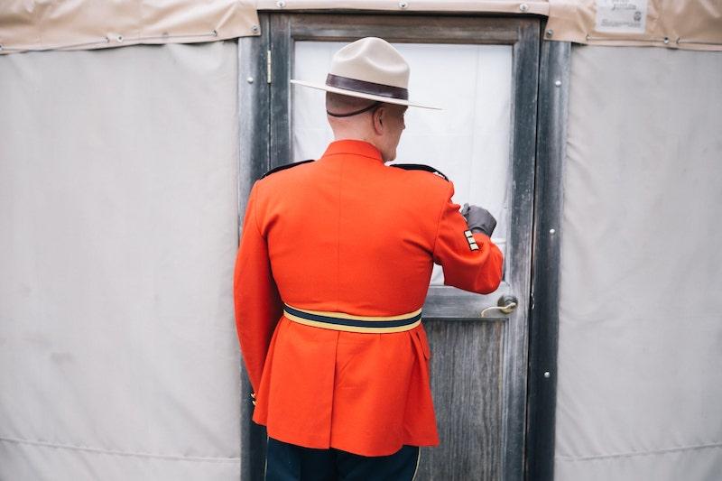 RCMP Groom knocking on door of yurt at merridale wedding venue on Vancouver Island. Taken by Marlboro Wang Photo for Focal bookfocal.com