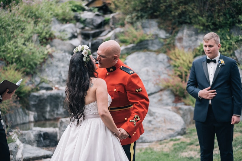 RCMP groom kissing bride at merridale wedding venue on Vancouver Island. Taken by Marlboro Wang Photo for Focal bookfocal.com
