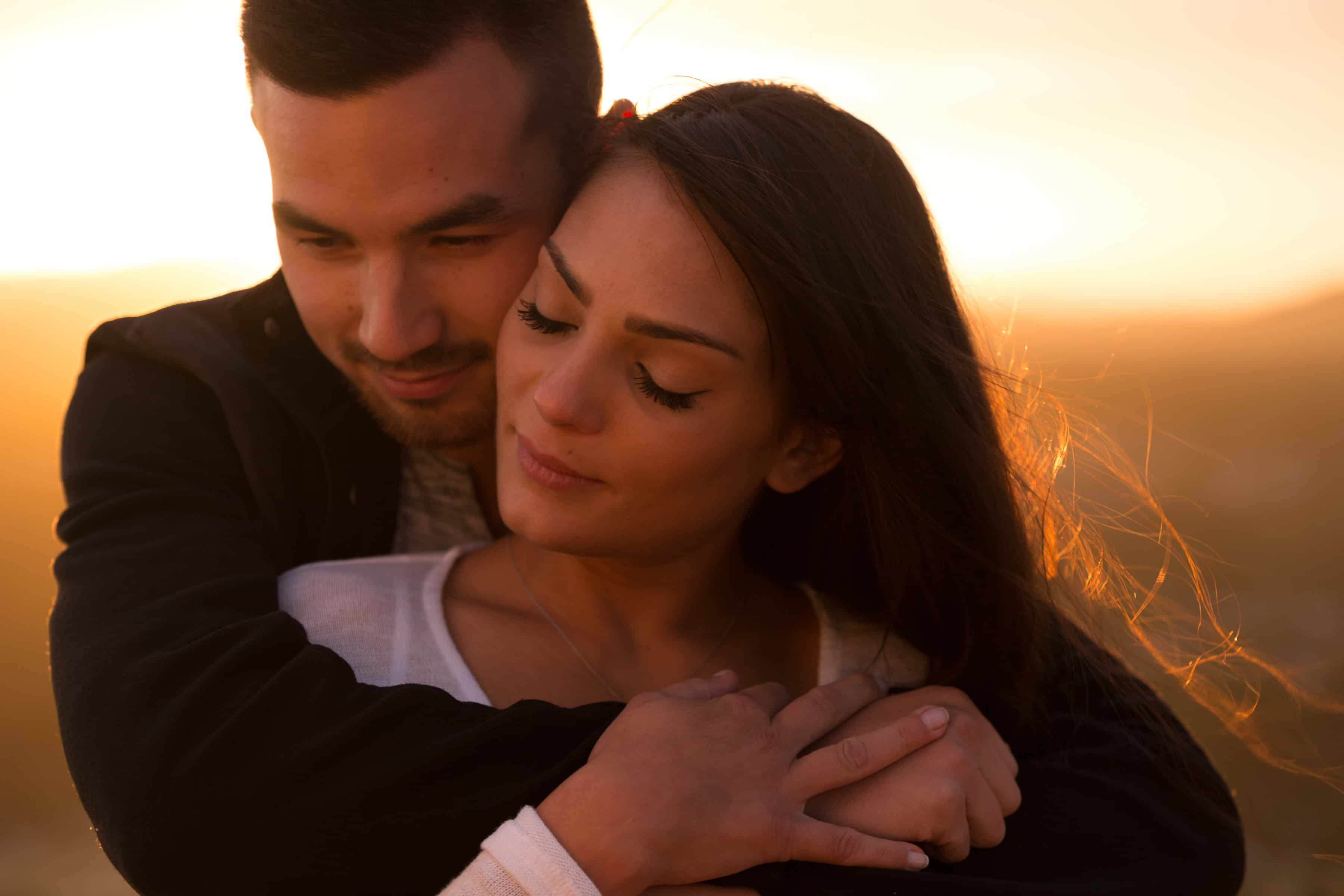 Couple embracing with sunset behind them