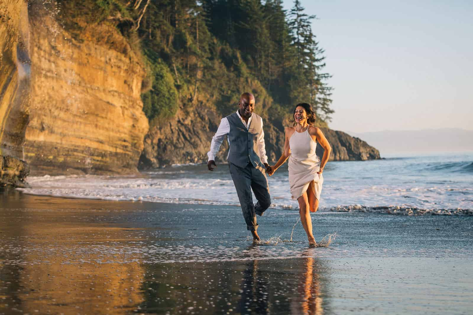 Newlyweds splash in the water at Mystic Beach in Juan de Fuca Provincial Park.