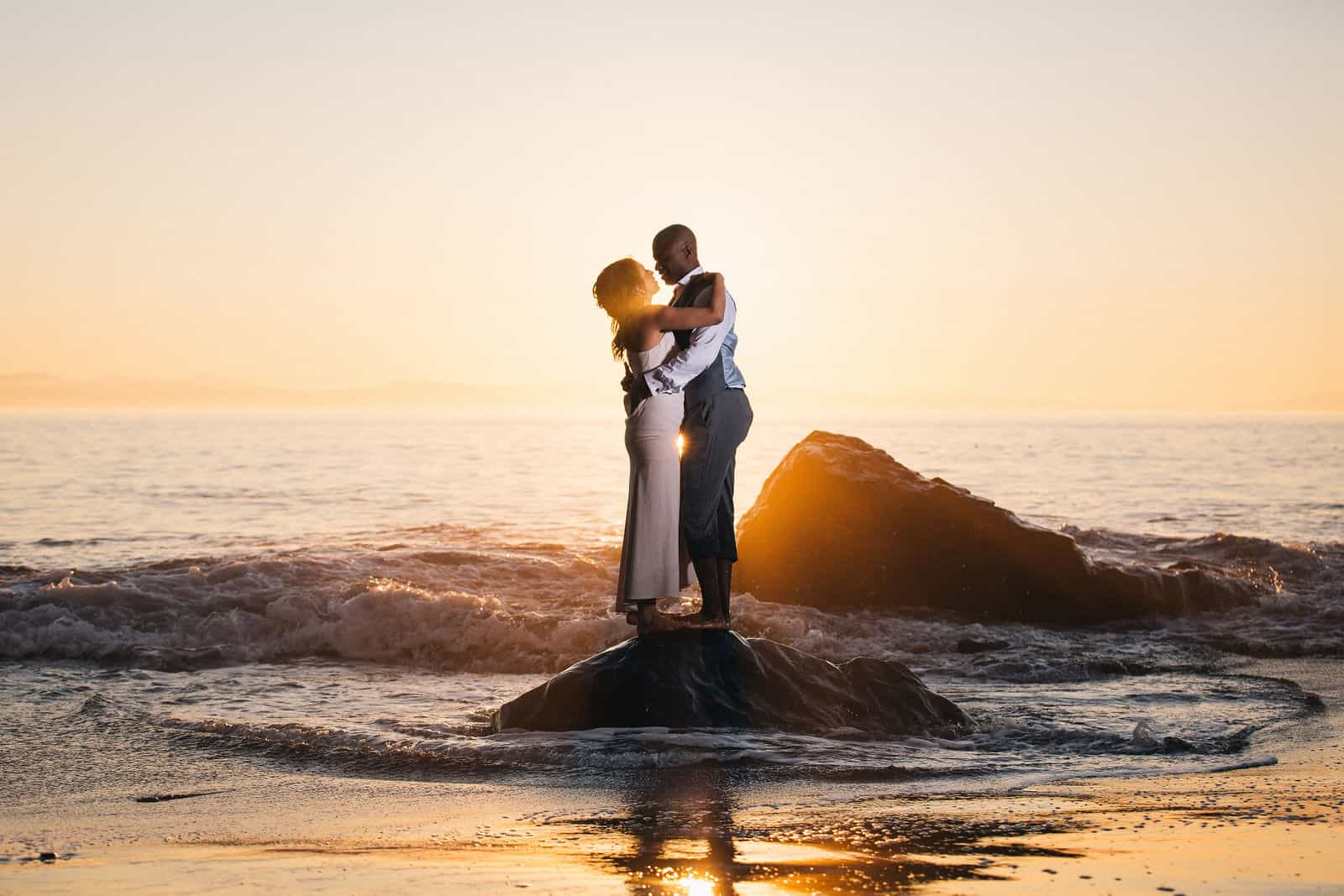 Newlyweds embrace in the evening light at Mystic Beach in Juan de Fuca Provincial Park.