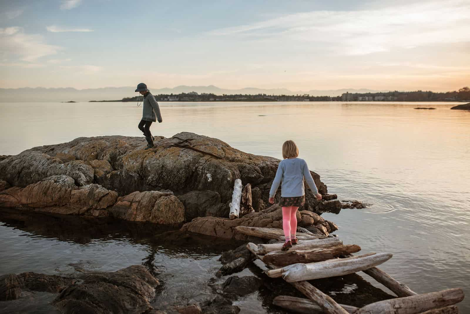 Family explores the rocky shoreline at Cattle Point in Victoria, BC.