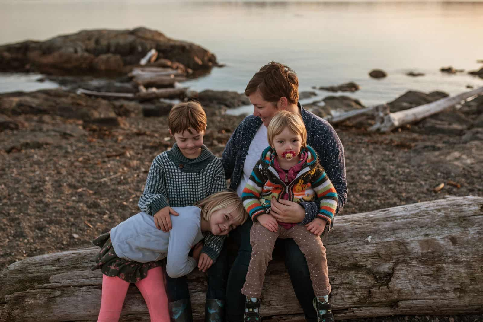 Family poses for a photo on a driftwood log at Cattle Point in Victoria, BC.