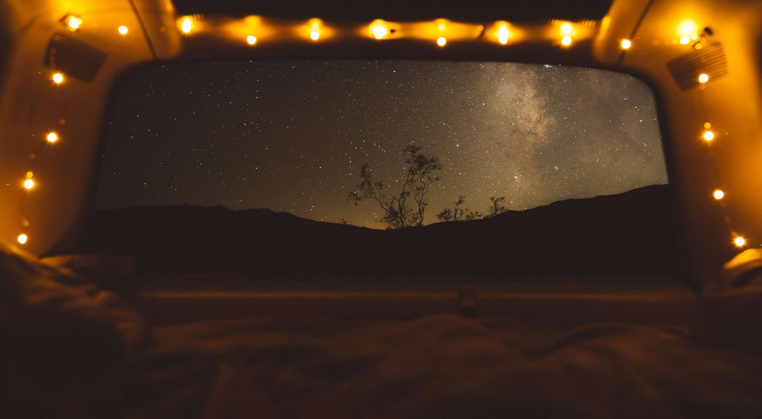 A starry night sky awaits beyond the open doors of a campervan.