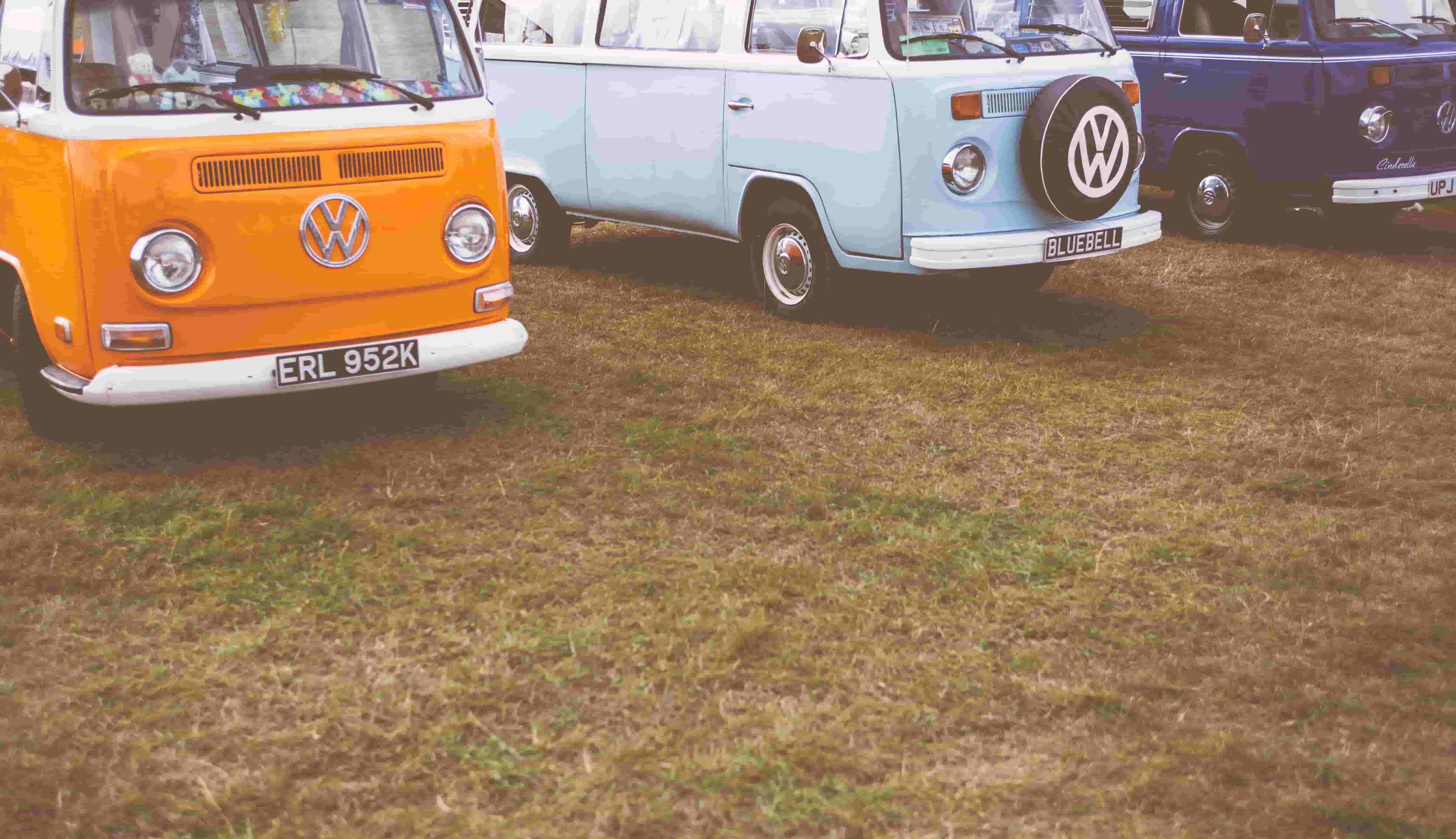 Volkswagen motorhomes park on a grassy lot.