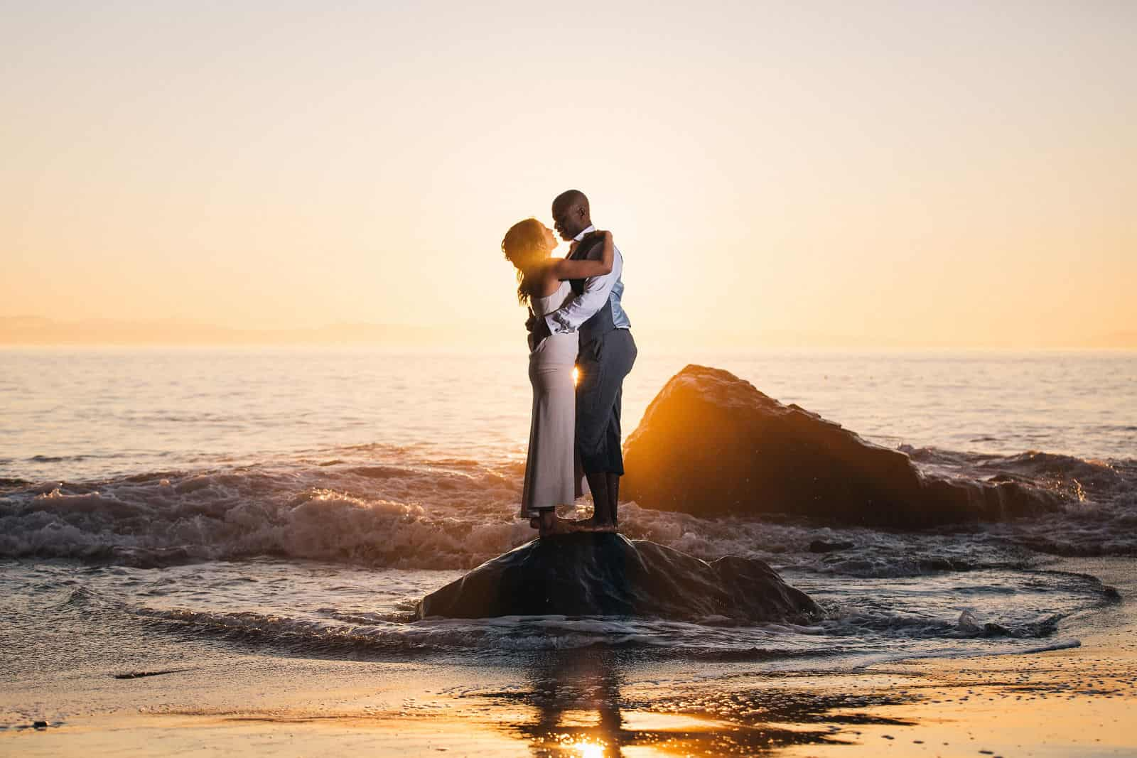 A newlywed couple embraces in the evening light by the ocean.