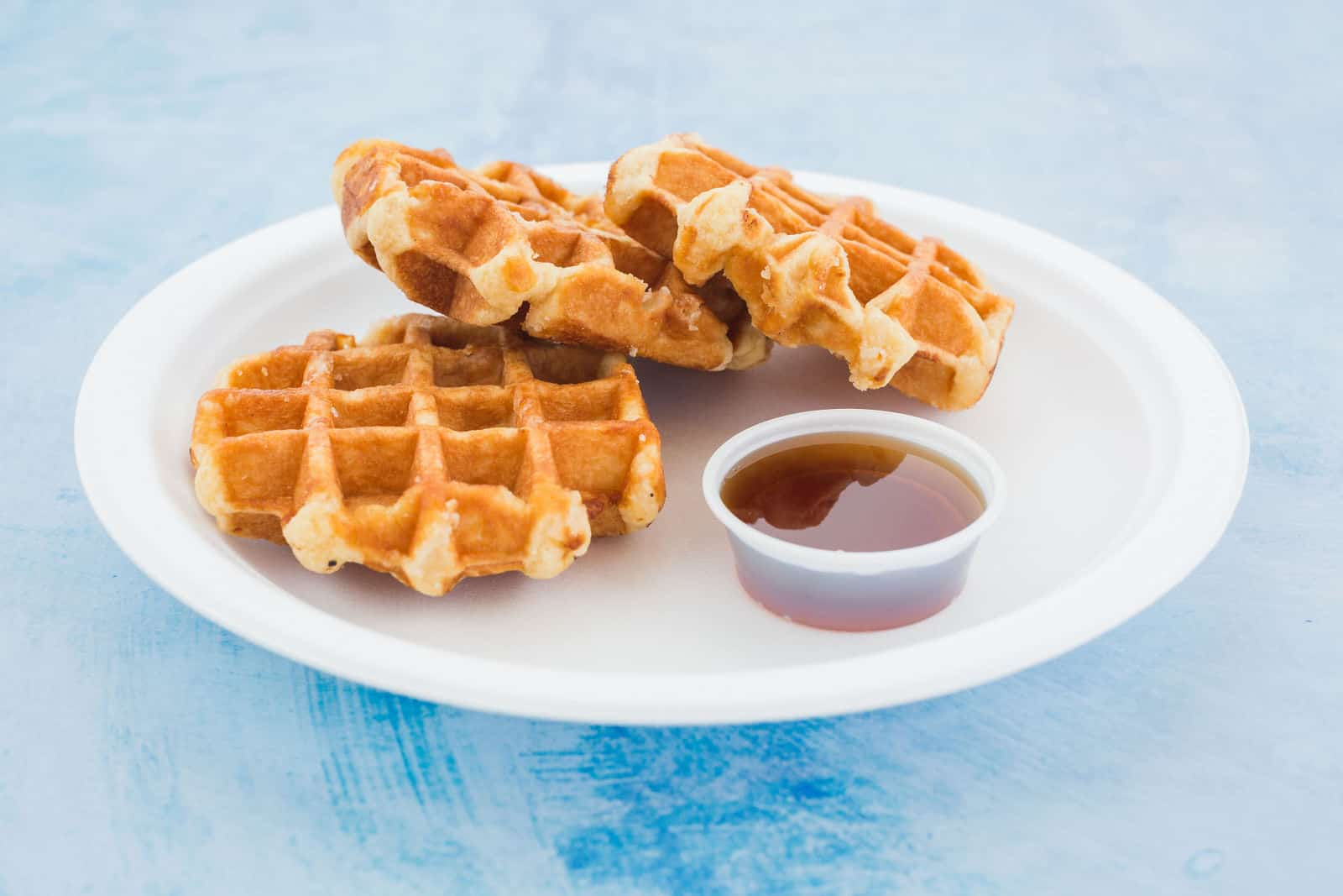 A trio of waffles tantalize on a plate.