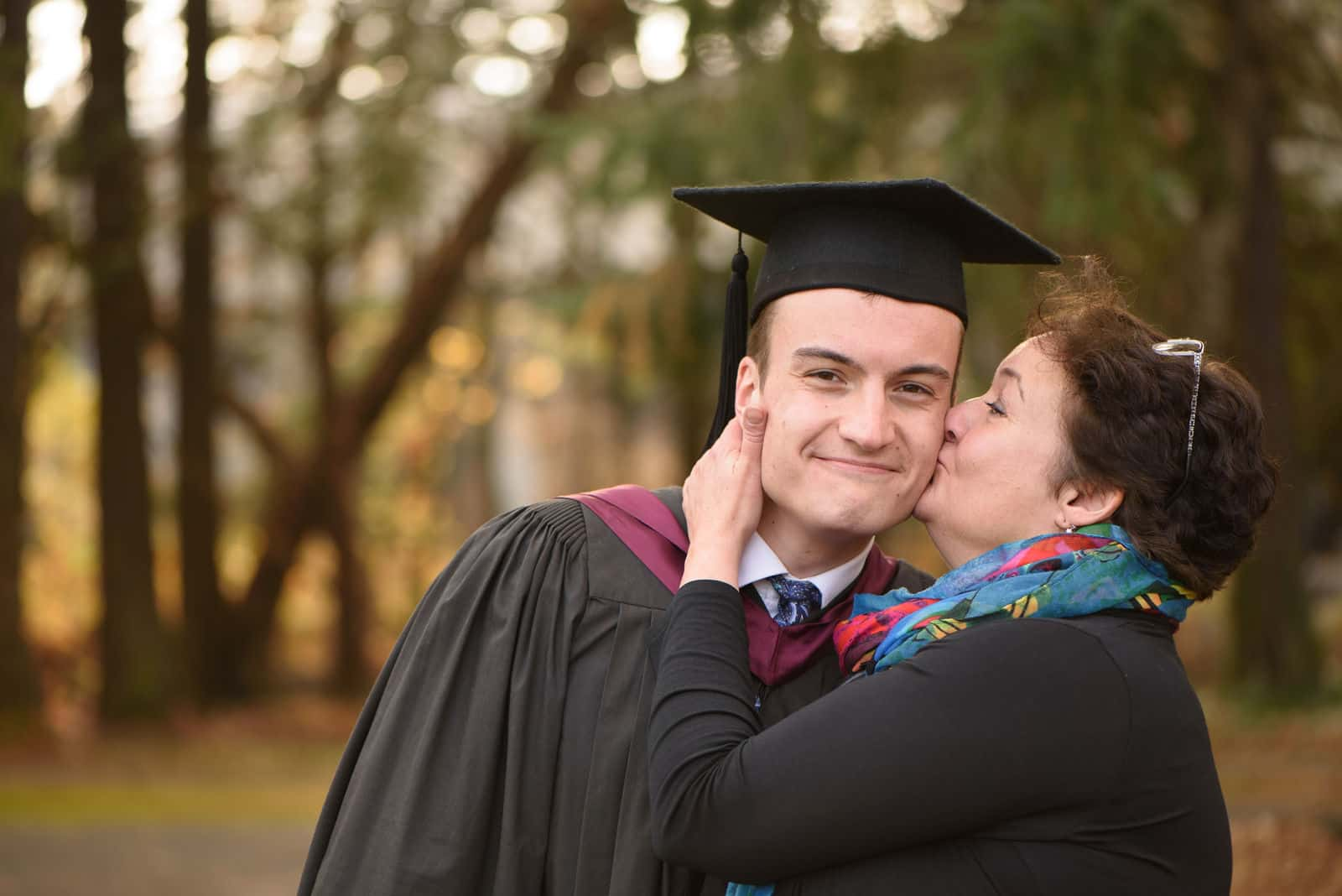 A mother kisses her son at graduation.