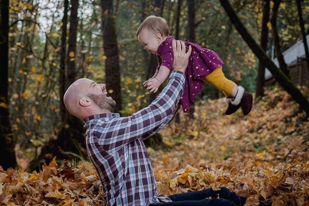 A father and daughter play in the autumn leaves.