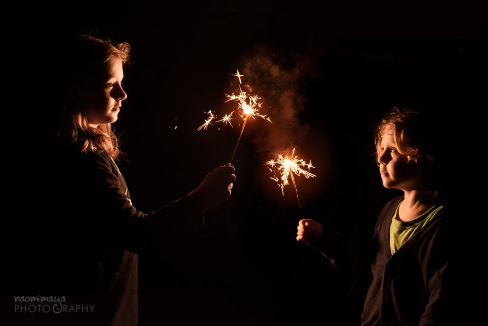 Two children hold sparklers in the night. Photograph by Naomi Maya Photography.
