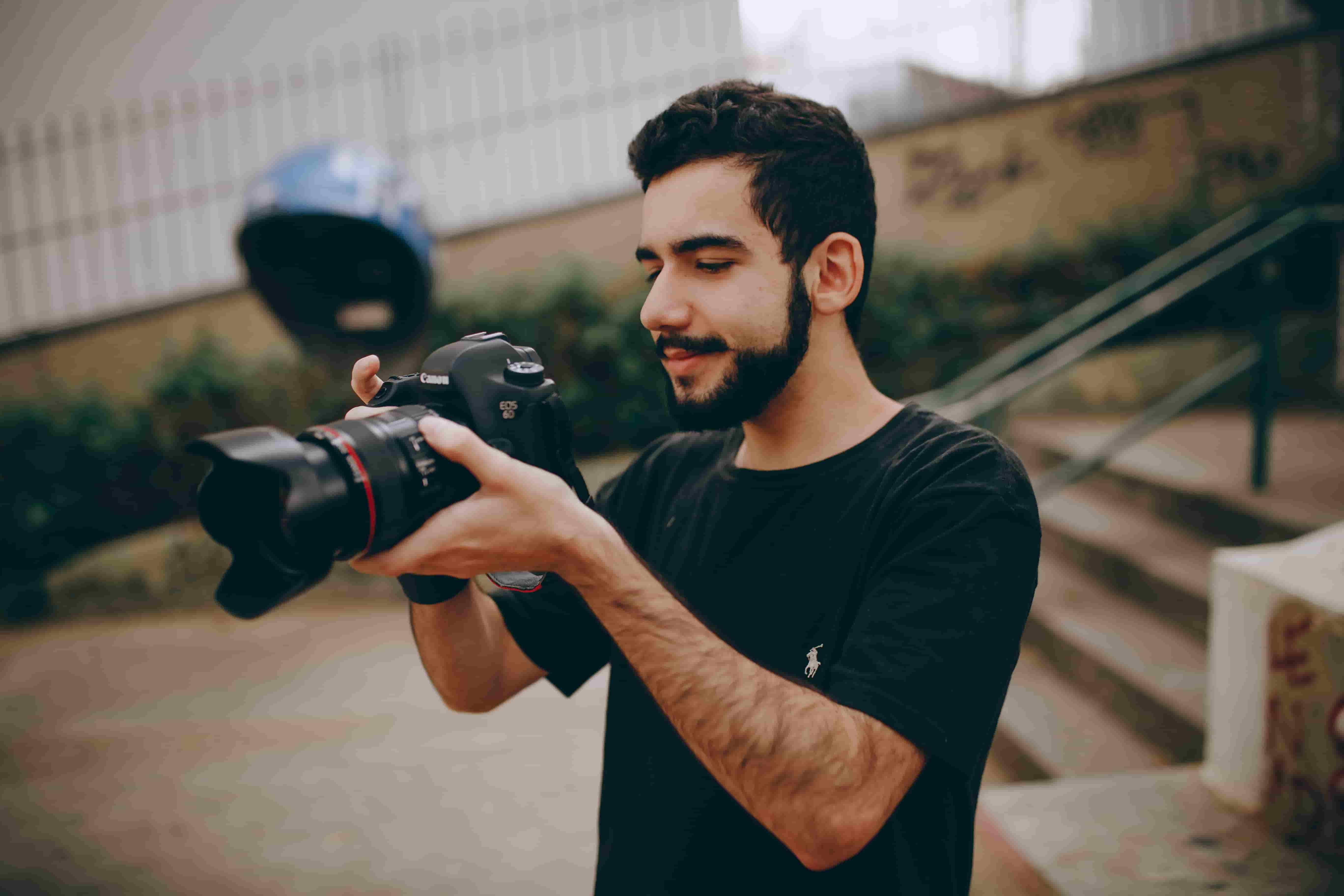 A photographer checks the screen of their Canon DSLR camera.