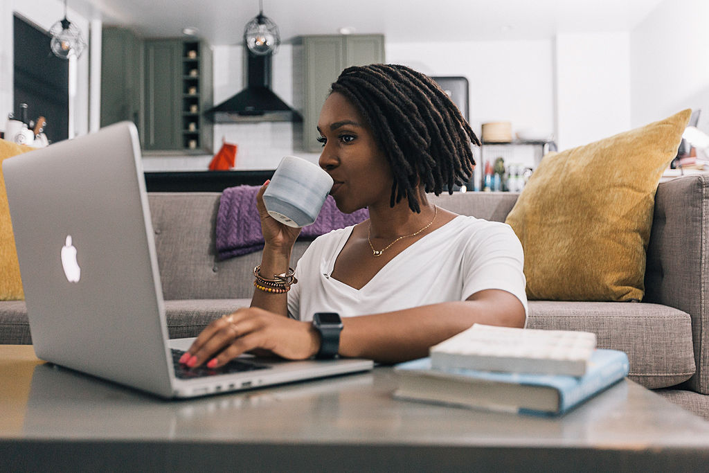 Woman drinking coffee while on her laptop
