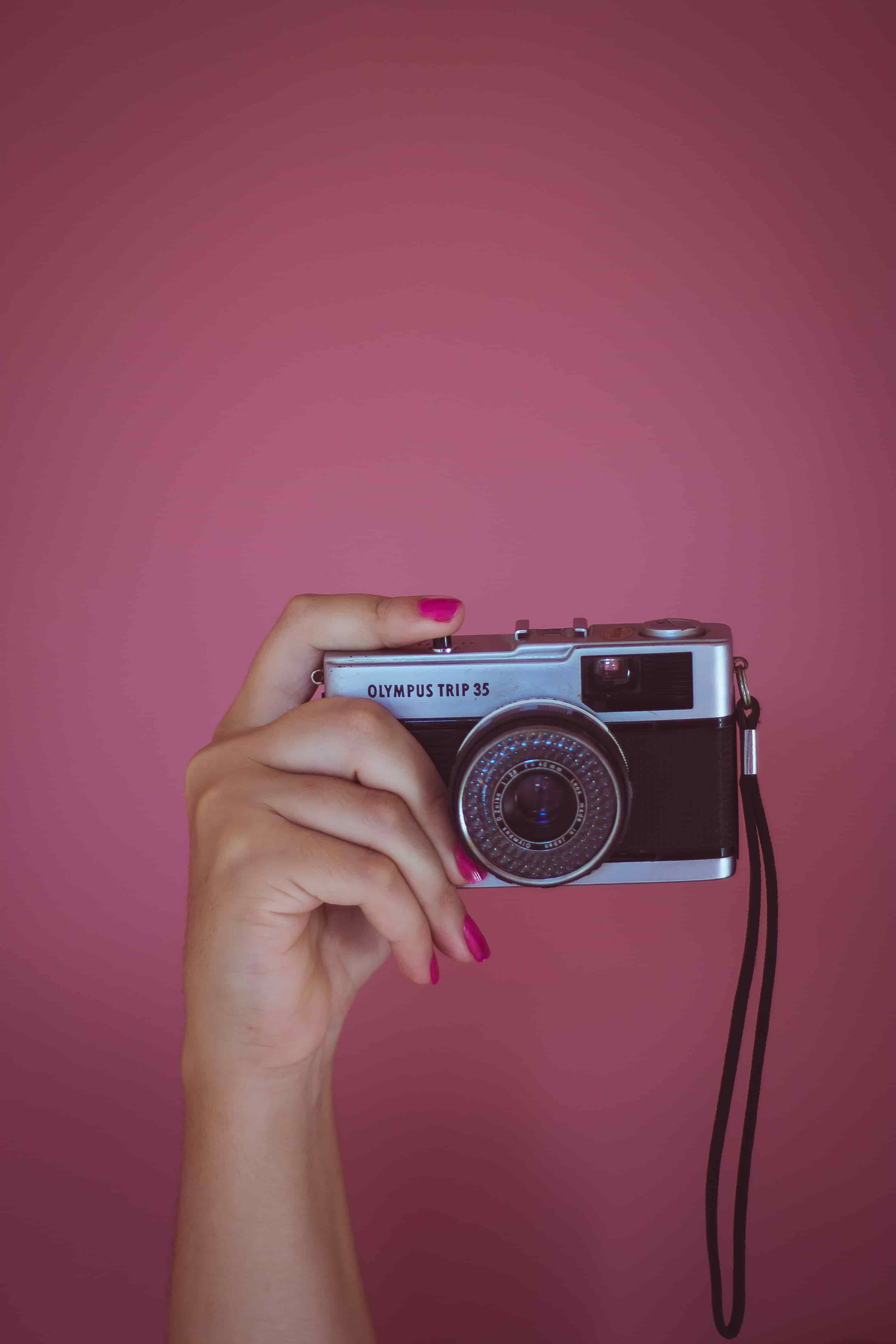 A finger presses the shutter of a black Olympus camera. Ask Marlboro: Should I charge for photos on top of my session fees?