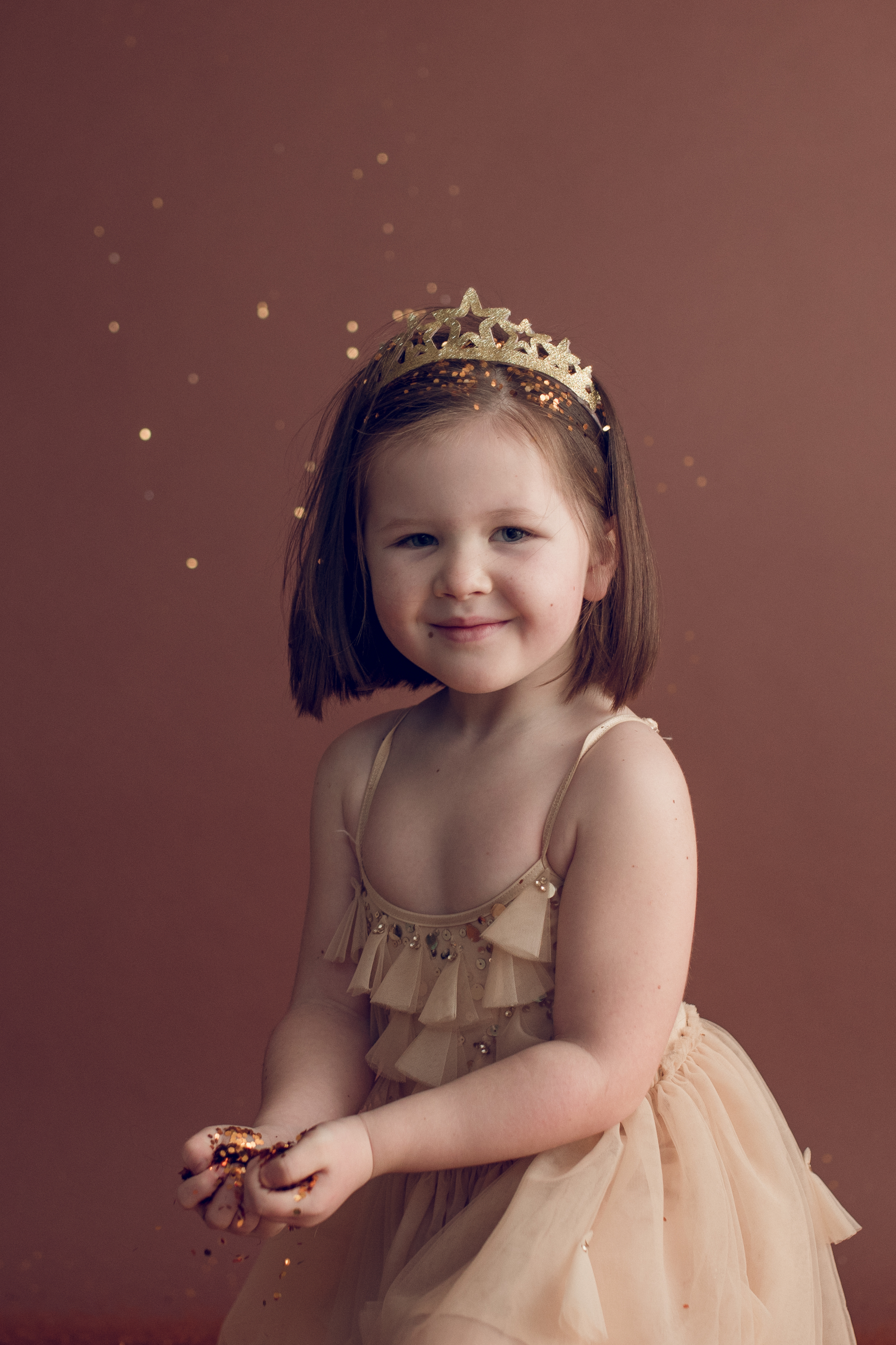 Young girl in pink dress holding glitter