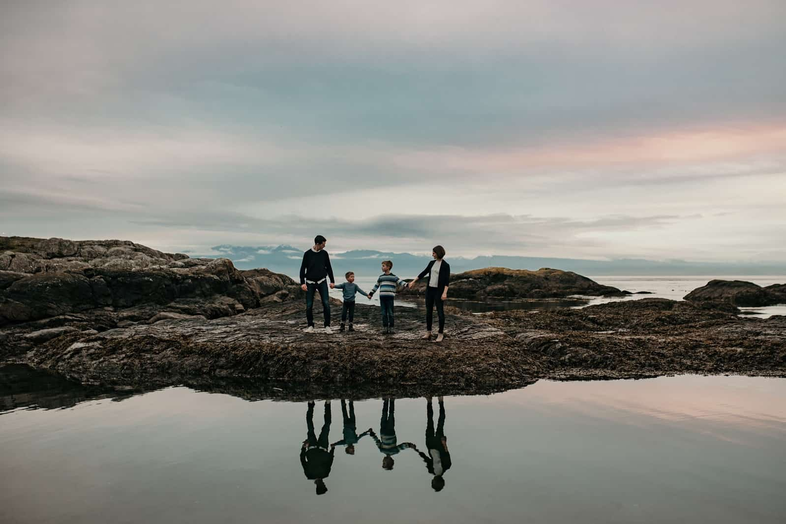 A family holds hands, reflection captured in the water, in front of Dallas Beach in Victoria, BC.