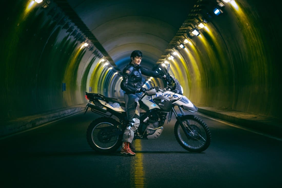 A female motorcyclist poses for a photo in an empty road tunnel.