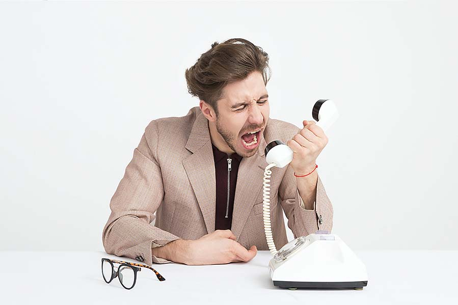 A businessman screams into a telephone. Photo by Moose Photos