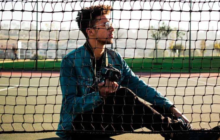 A photographer plans their next shot, sitting behind a tennis net.
