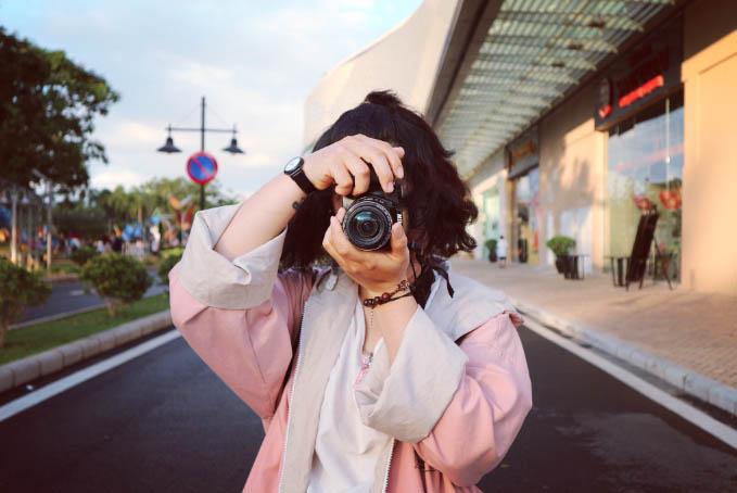 A photographer peers through a camera lens.