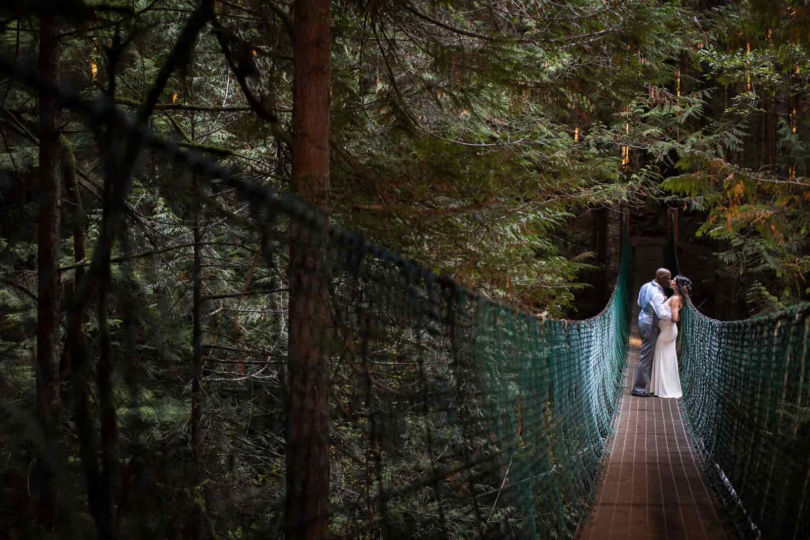 A newlywed couple shares a kiss on a suspension bridge. Photo by Marlboro Wang.