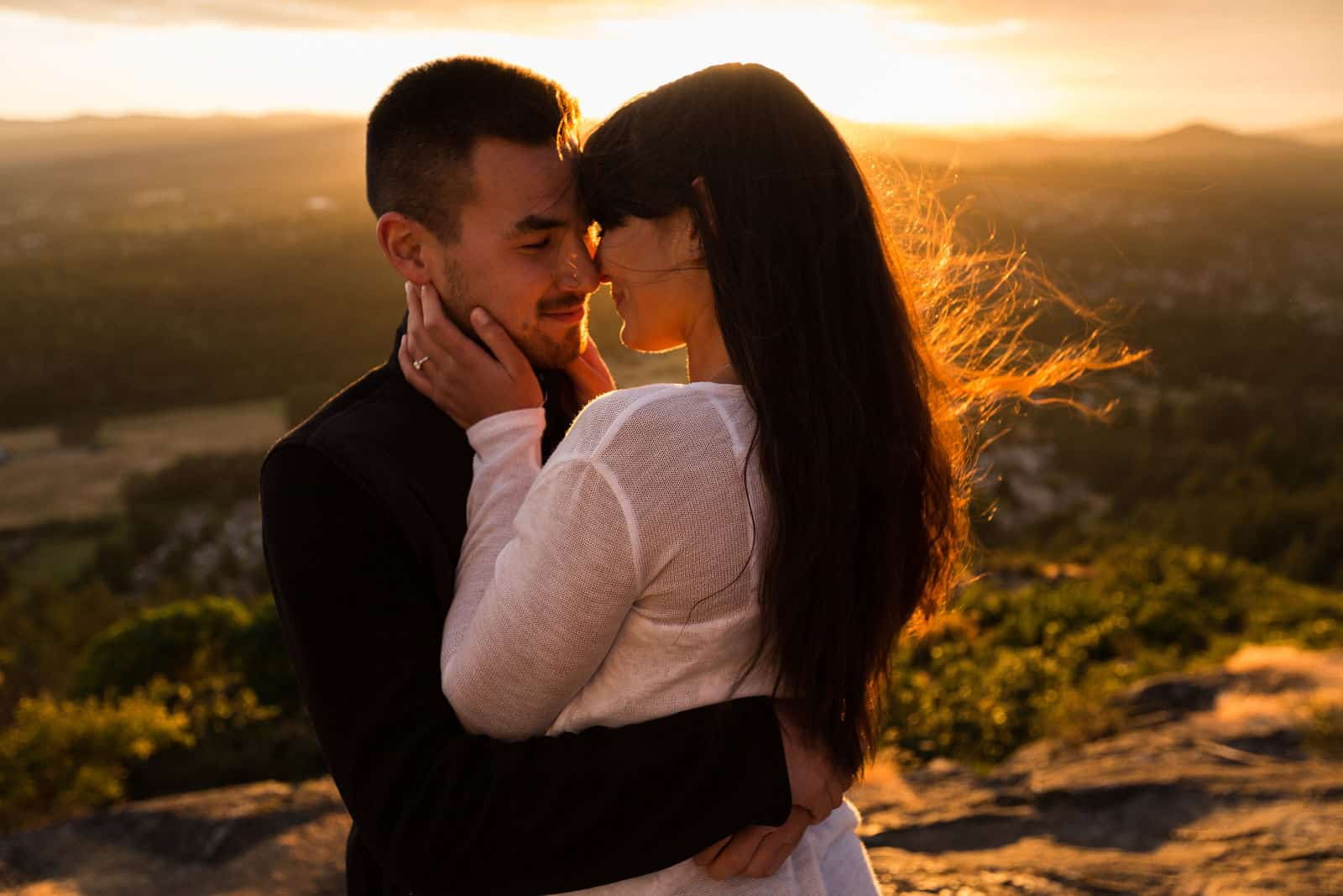 A young couple embraces during golden hour. Photo by Marlboro Wang.