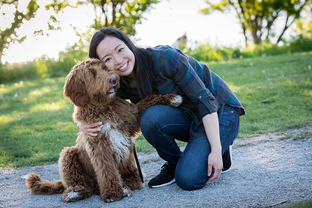 A woman poses with her labradoodle for a photo