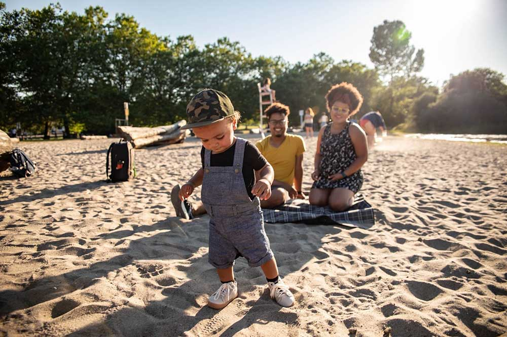 A young boy plays at the beach in Vancouver's Trout Lake while his parents watch.