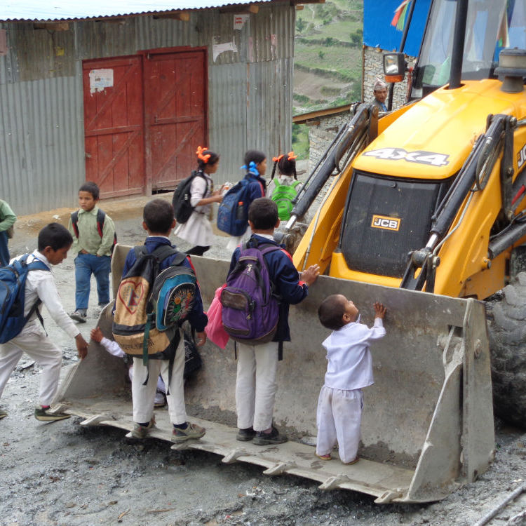 Children standing on digger on road