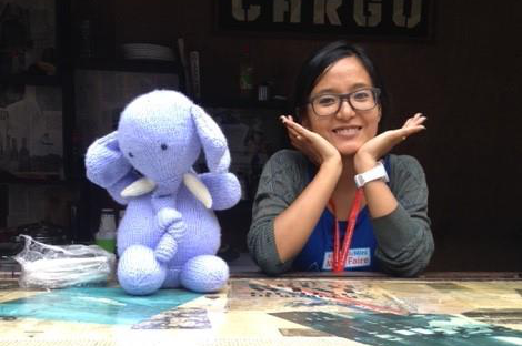 Woman smiling beside knitted elephant Safetyknot mascot