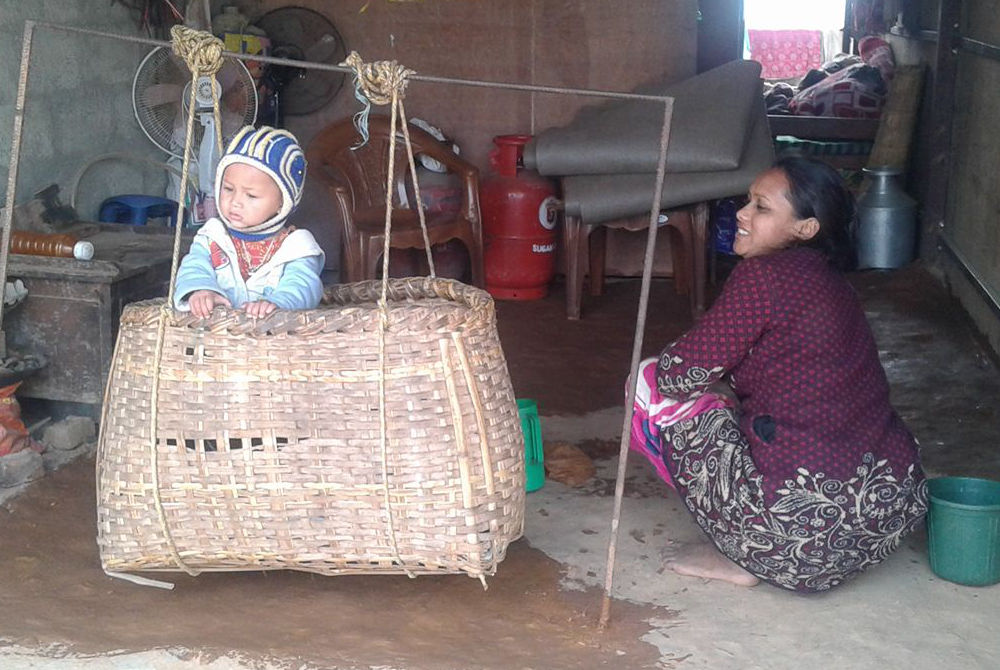 Nepali woman with baby in straw crib