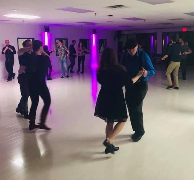 Several couples dancing at a social dance.