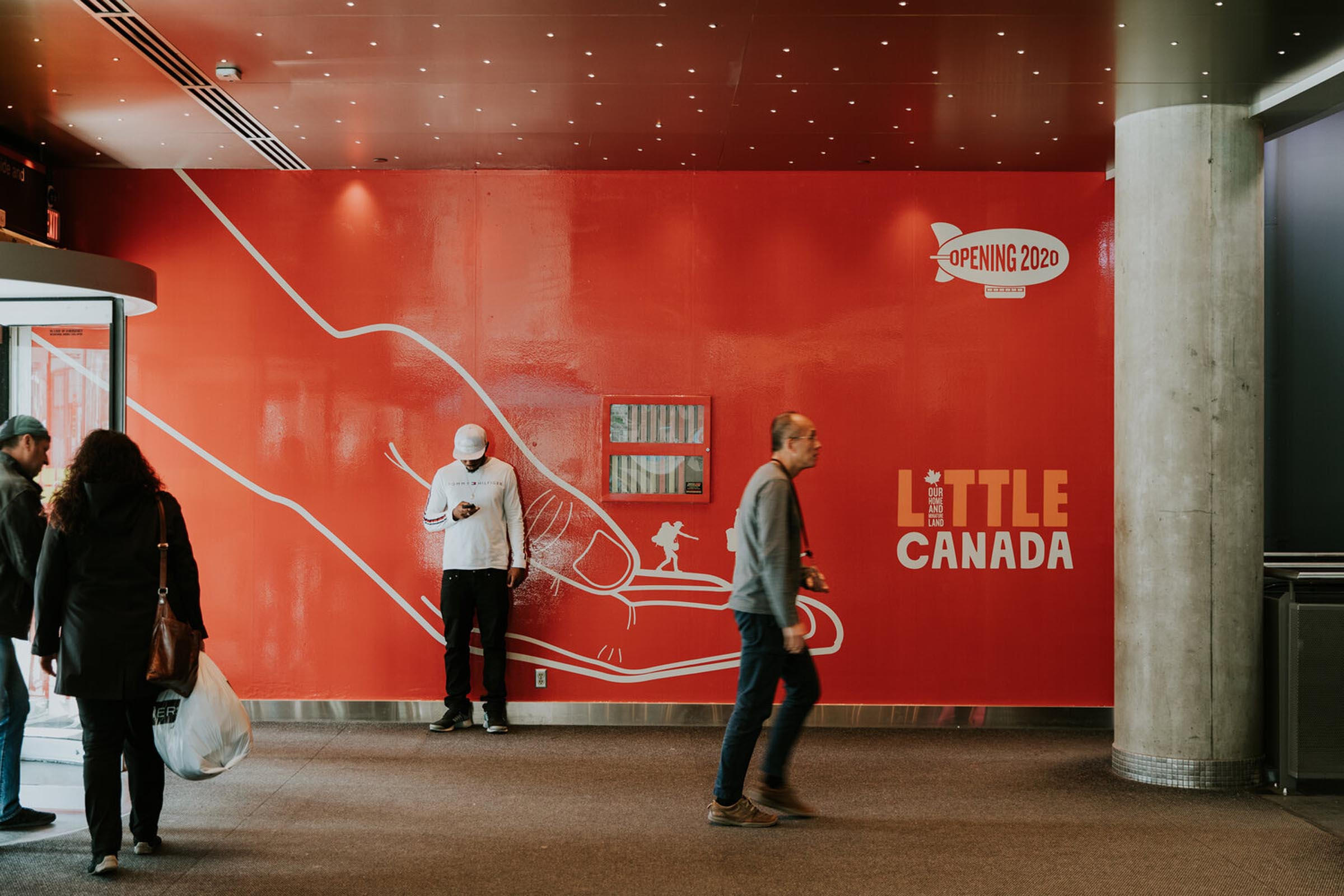Photo of man walking past Little Canada outdoor mural